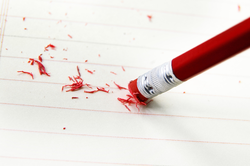 lined paper with red pencil erasing